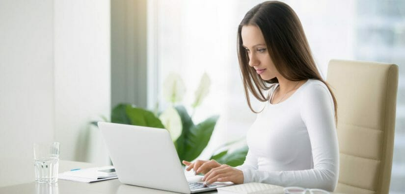 Picture of a woman on a laptop completing online surveys.